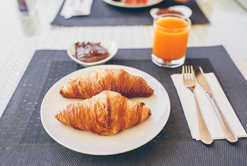 Fresh and delisious breakfast in hotel restaraunt. Delicious tasty croissants and fresh juice for breakfast at outdoor cafe royalty free stock image