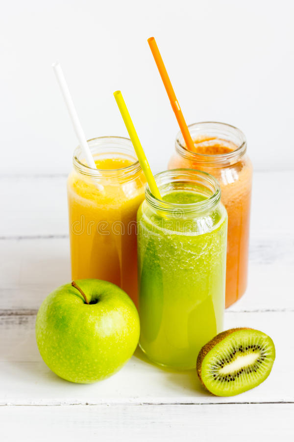 Fresh detox juices in glass bottles on white background.  stock photography