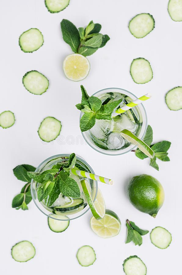 Fresh detox spring cocktail with mint, lime, ice, cucumber, straw on soft white wooden board as fun summer holiday background. royalty free stock images