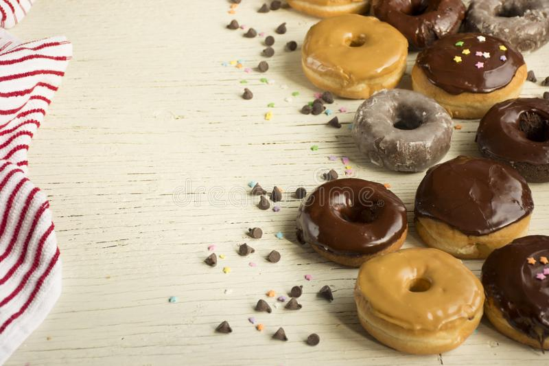 Fresh Donuts in a box. Donuts. Fresh Donuts on a white wooden background with a coffee cup stock photo