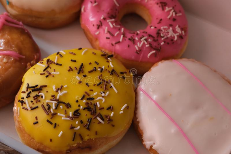Fresh donuts with colorful glaze in the box. Many Assorted donuts on a background royalty free stock image