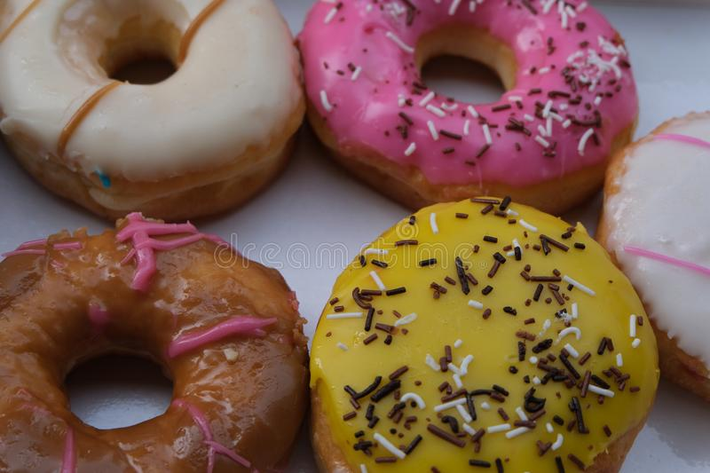 Fresh donuts with colorful glaze in the box. Many Assorted donuts on a background royalty free stock photos