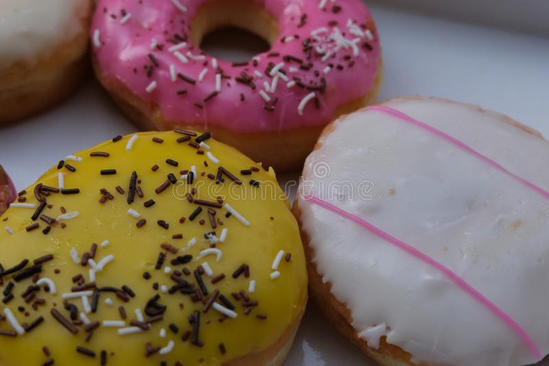 Fresh donuts with colorful glaze in the box. Many Assorted donuts on a background royalty free stock photography