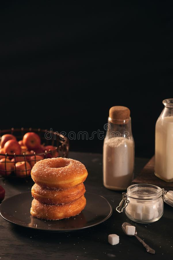 Fresh donuts with sugar powder and coffee with milk on a wooden table. Breakfast in the village royalty free stock photos