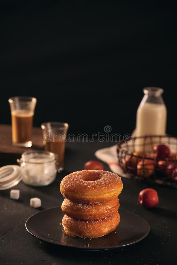 Fresh donuts with sugar powder and coffee with milk on a wooden table. Breakfast in the village.  stock images