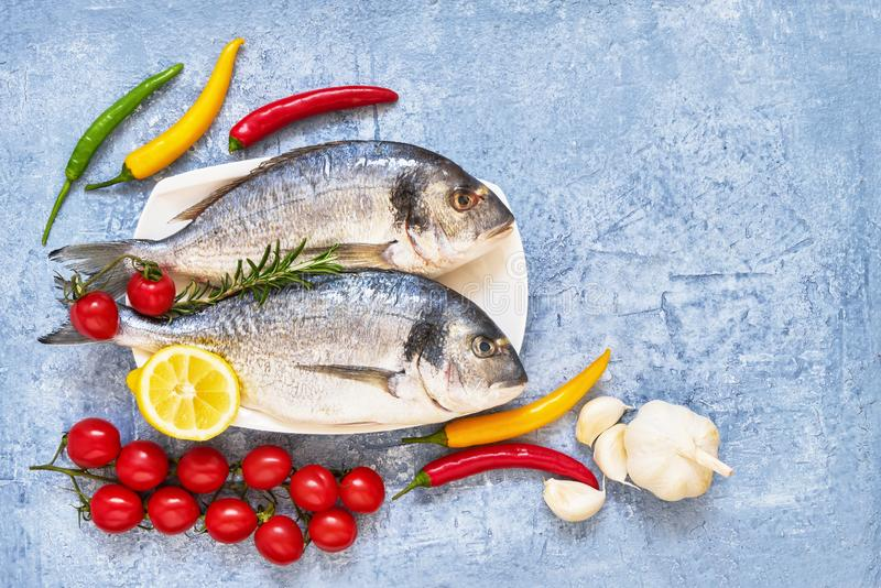 Fresh dorada fish with spices on wooden cutting board. Healthy food concept. Top view, copy space. Mediterranean seafood concept stock photos