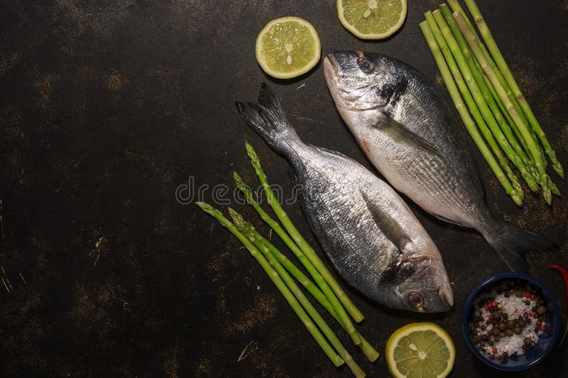 Fresh dorado fish with asparagus and spices, ingredients for cooking on a dark background. Top view, place for text, flat lay. stock images
