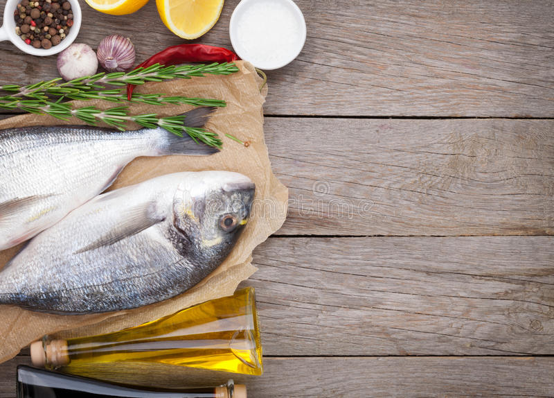 Fresh dorado fish cooking with spices and condiments. On wooden table with copy space stock photos