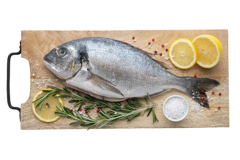 Fresh dorado fish with lemon slices, salt and rosemary on cutting board. Top view, . stock photography