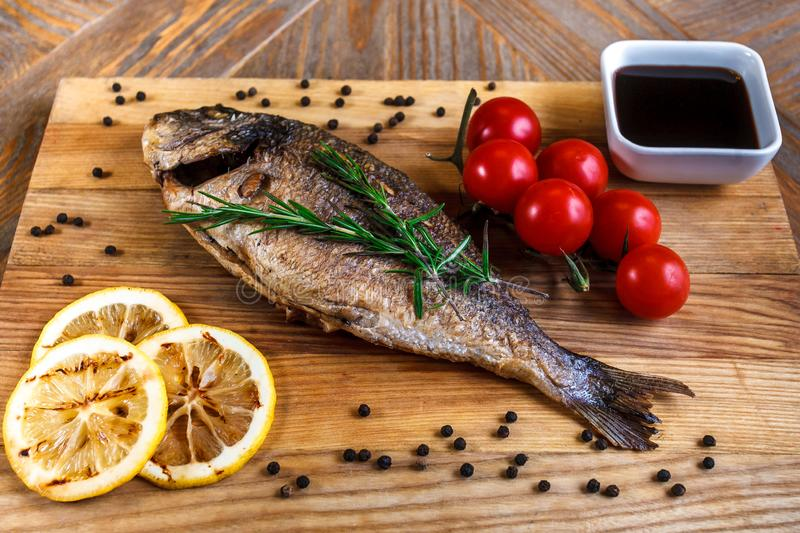 Fresh dorado grill with lemon and cherry tomatoes on a wooden tray. For restaurant menu or recipe.  stock photo