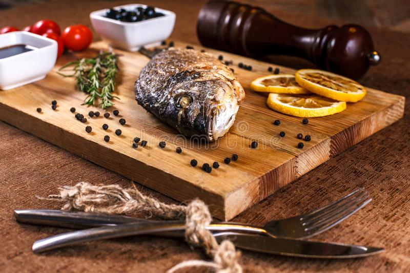 Fresh dorado grill with lemon and cherry tomatoes on a wooden tray. For restaurant menu or recipe.  stock images