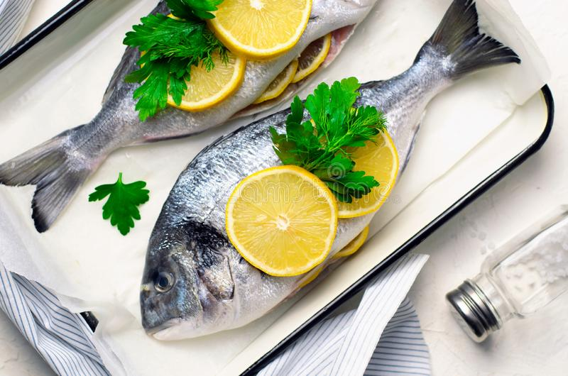 Fresh Dorado or Sea Bream with Lemon and Herbs, Raw Fish Ready to be Cooked, Top View. Fresh Dorado or Sea Bream with Lemon and Herbs, Fish in Baking Tray Ready royalty free stock images