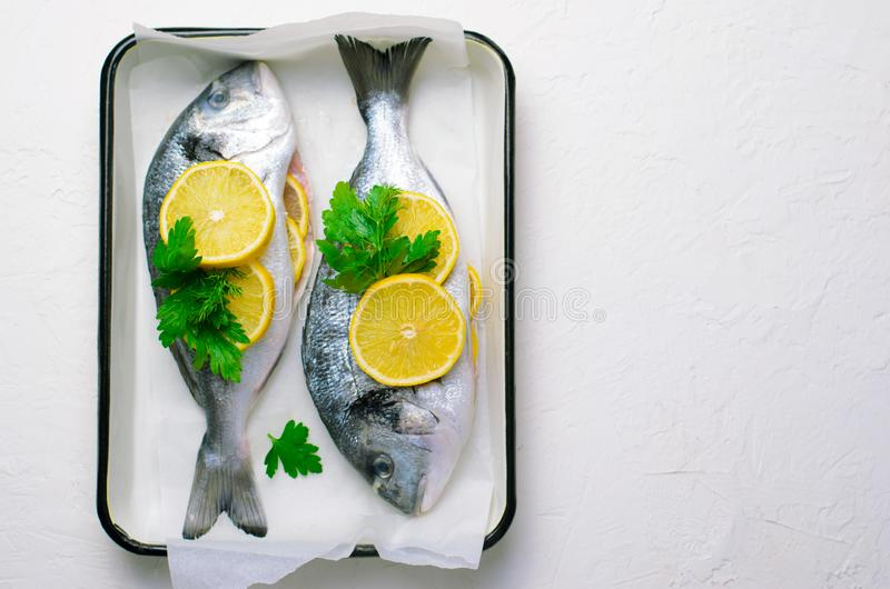 Fresh Dorado or Sea Bream with Lemon and Herbs, Raw Fish Ready to be Cooked, Top View stock photo
