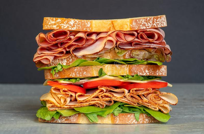 Fresh double layered sandwich with ham, lettuce, tomatoes, cheese on a toast bread, on black background. Fresh double layered sandwich with ham, lettuce stock photo