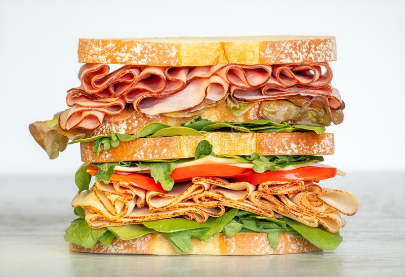 Fresh double layered sandwich with ham, lettuce, tomatoes, cheese on a toast bread. Food background stock images
