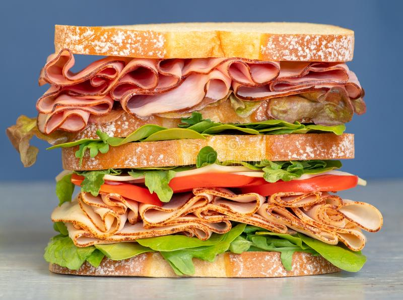 Fresh double layered sandwich with ham, lettuce, tomatoes, cheese on a toast bread. Food background. Close up. Very delicious sub sandwich. Fast food. Magazine stock photography