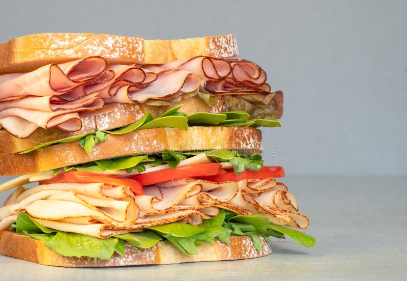 Fresh double layered sandwich with ham, lettuce, tomatoes, cheese on a toast bread. Food background. Close up. Very delicious sub sandwich. Fast food. Magazine stock photos