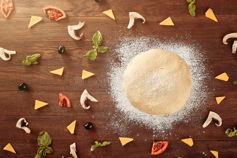 Fresh dough prepared for pizza with tomatoes and sliced pepper on a wooden board stock photos
