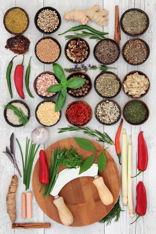 Fresh and Dried Herbs and Spices. Fresh and dried herb and spice sampler with chopper and board over distressed white wooden background royalty free stock image