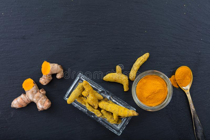 Fresh and dried turmeric roots and powder on black background. Top view, copy space royalty free stock photo