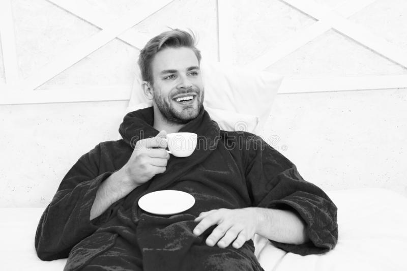 A fresh drink for breakfast. Happy man drinking coffee for breakfast. Handsome guy enjoying his breakfast drink in bed royalty free stock images