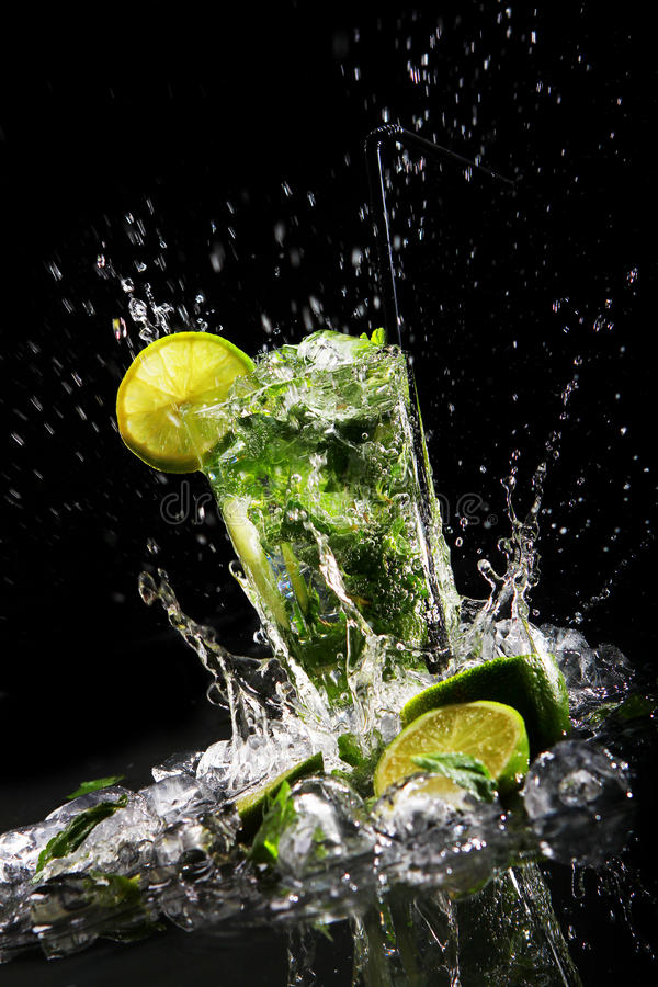 Fresh drink with green lime. Fresh drink with splashes of water, green mint and lime on black background stock photography