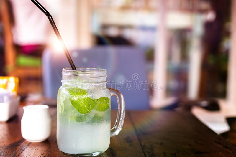 Fresh drink lemonade mojito on wooden table. Mojitos with mint leaves, lime and ice, outdoor. stock image