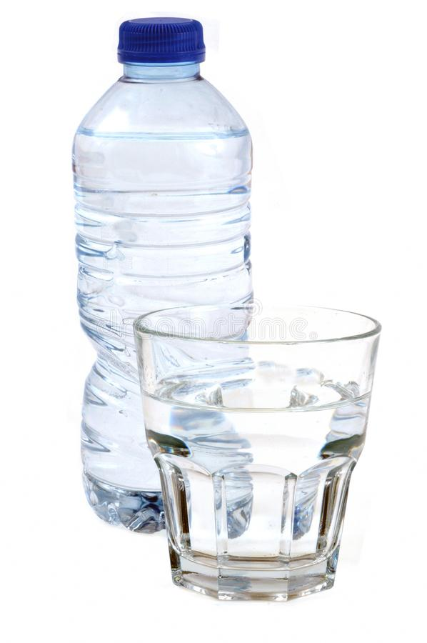 Bottle and glass of mineral water in closeup on white background. Fresh drink in a plastic bottle next to a glass of water stock image