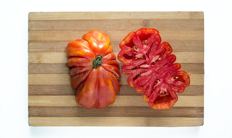 Fresh ecologic beefsteak tomato. Fresh ecologic beefsteak tomato in a rustic table royalty free stock images