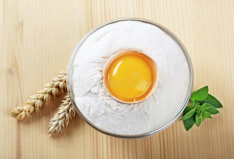 Fresh egg in a bowl of flour stock photography