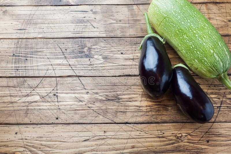 Fresh eggplant and zucchini on wooden background with copy space.  stock photos