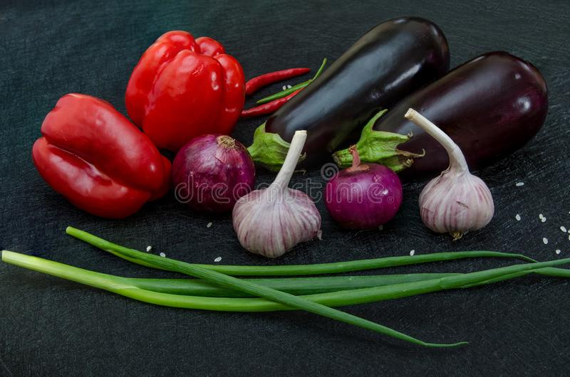 Fresh eggplants, pepper, garlic, onion on black background royalty free stock photo