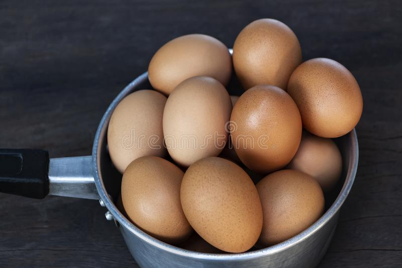 Fresh eggs are in a pot on a wood table stock images
