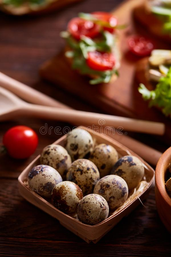 Fresh eggs of a quail with tomato and bowl of paste on wooden table, selective focus, close-up stock photography