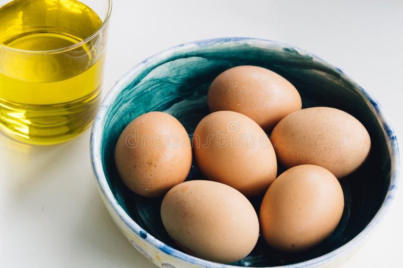 Fresh eggs an virgin olive oil stock photos