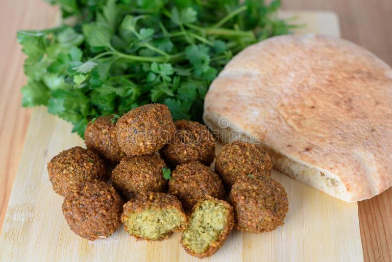 Fresh falafel balls, pita bread and parsley on a wooden cutting board royalty free stock photo