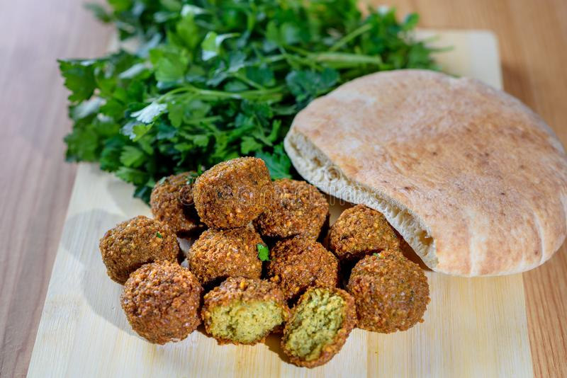 Fresh falafel balls, pita bread and parsley on a wooden cutting board stock photography
