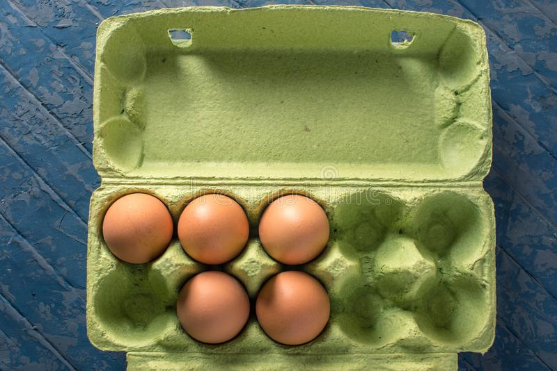 Fresh farm eggs in green tray, on beautiful dark background. Home eco-friendly products stock photo