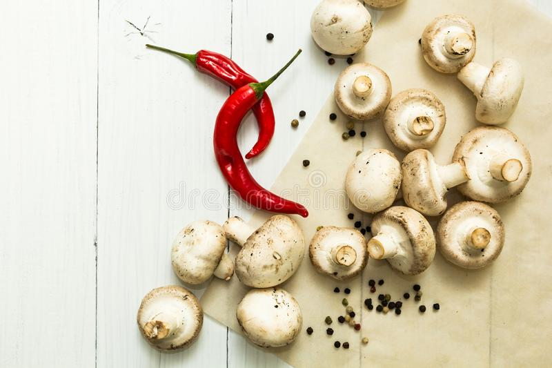 Fresh farmers ceps and red chili pepper on white table, organic food stock images