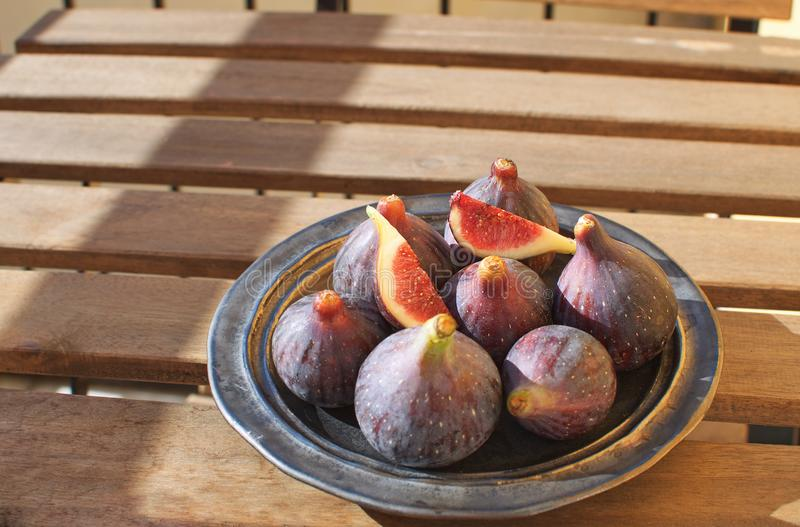 Fresh figs on ceramic black plate Wooden table Sunligh Copy space Autumn harvesting F. All stock image
