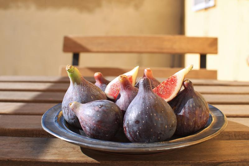 Fresh figs on ceramic black plate Wooden table Sunligh Copy space Autumn harvesting F. All stock photo