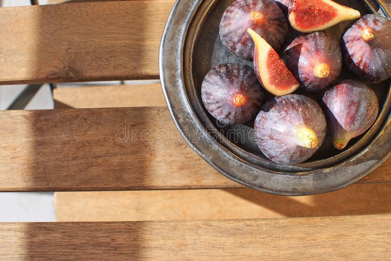 Fresh figs on ceramic black plate Wooden table Sunligh Copy space Autumn harvesting F. All Top view royalty free stock image