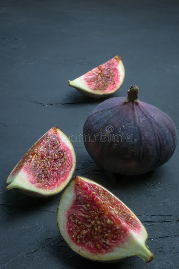 Fresh figs. Food photography. Creative scheme of whole and sliced figs on a dark background. Copy space. stock images