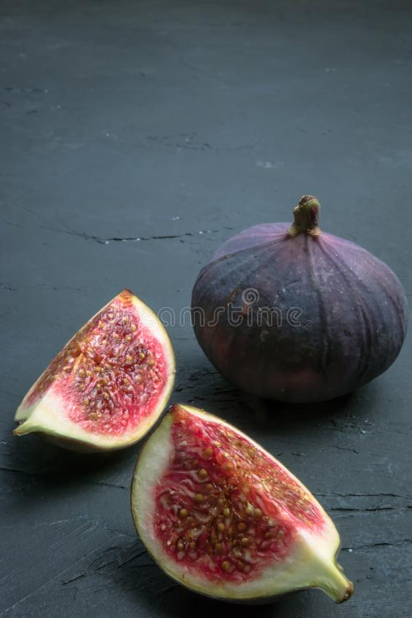 Fresh figs. Food photography. Creative scheme of whole and sliced figs on a dark background. Copy space. Fresh figs. Food photography. Creative scheme of whole royalty free stock image