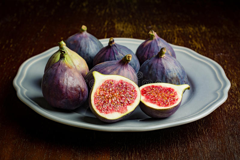 Fresh figs. On gray plate, close up, selective focus, natural light stock photography