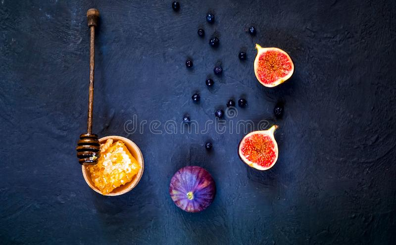 Fresh figs and honeycombs. Creative layout of the whole and sliced figs on dark blue background. Flat lay. Copy space, closeup. stock photography