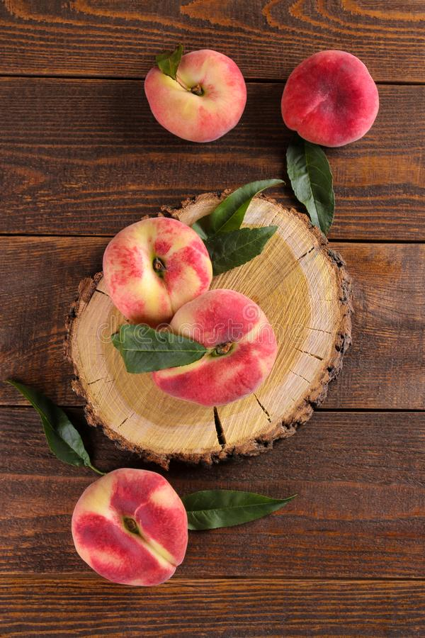 Fresh figs peach on a wooden pedestal on a brown wooden background. Top view stock photos