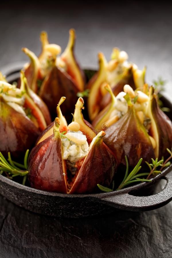 Fresh figs stuffed with gorgonzola cheese, pine nuts and herbs in a black dish on a dark, stone ground, close up. royalty free stock photography