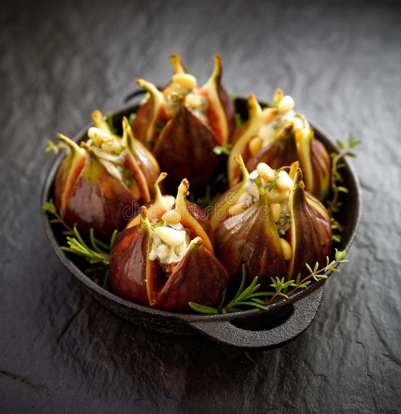 Fresh figs stuffed with gorgonzola cheese, pine nuts and herbs in a black dish on a dark, stone ground. Excellent, tasty, vegetarian snack royalty free stock photography
