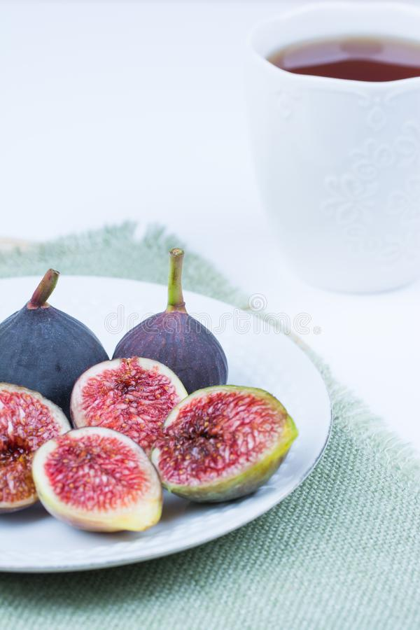 Fresh figs. Vegetarian Food. Whole and sliced figs on a white pl stock photography